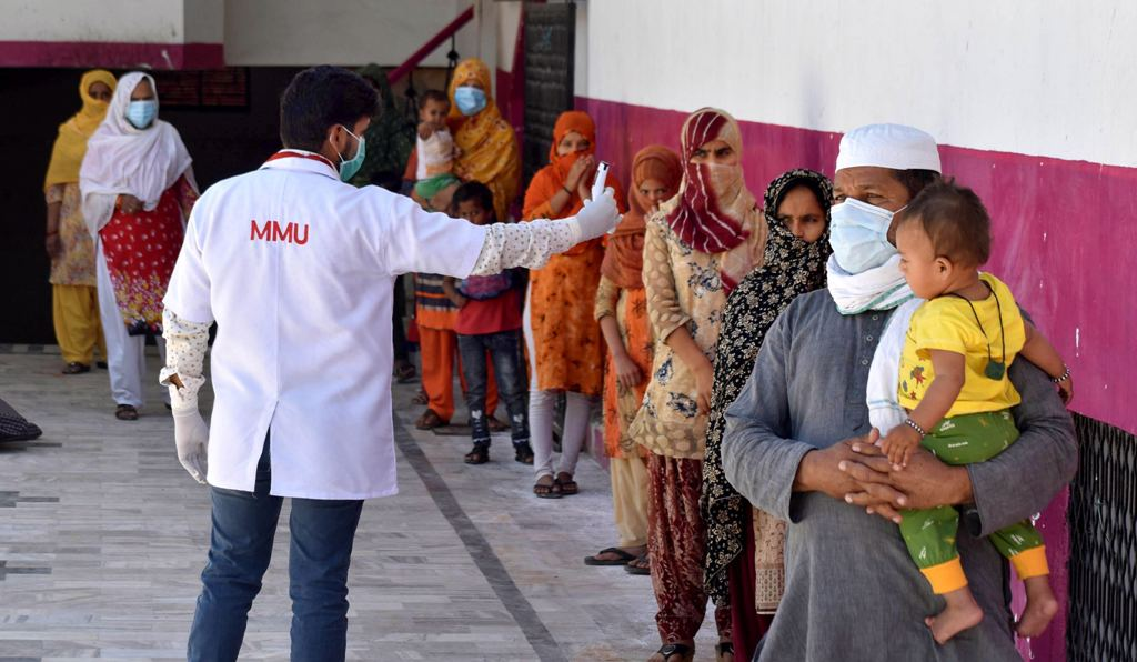 Prayagraj: A medics checks the temperature of attendees of a religious congregation in Delhis Nizamuddin area during their isolation period at a COVID 19 quarantine facility in Prayagraj, Friday, April 3, 2020. So far, around 400 COVID-19 positive cases and about 12 deaths in the country were found to have links with the Nizamuddin Markaz. (PTI Photo)(PTI03-04-2020 000121B) *** Local Caption ***