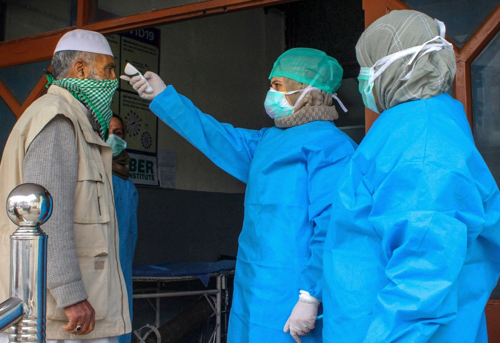 Srinagar: Doctors wearing protective gear scan visitors at the entrance of a hospital in wake of coronavirus outbreak, during the nationwide lockdown, in Srinagar, Thursday, April 2, 2020. (PTI Photo)(PTI02-04-2020_000173B)