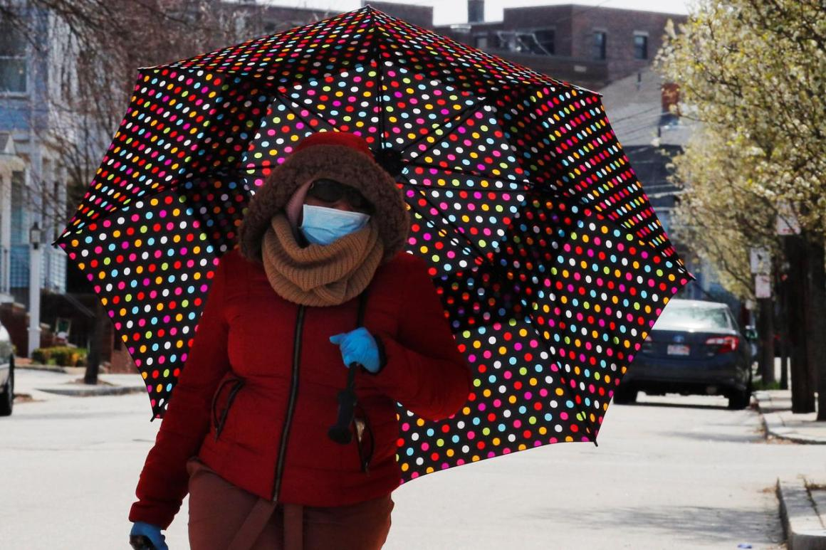 A woman walks under a large umbrella amid the coronavirus disease (COVID-19) outbreak in Medford, Massachusetts, U.S., April 12, 2020. REUTERS/Brian Snyder