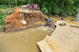 Kamrup: Villagers try to cross a damaged road which was washed away by flood water at Sukunia village in Kamrup district, Tuesday, May 26, 2020. Due to heavy rainfall from last few days, hundreds of villages in lower Assam have been affected by floods. (PTI Photo)(PTI26-05-2020_000194B)