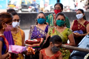 Mumbai: Hindu married women, wearing face masks amid concerns over COVID-19 outbreak, wait to perform rituals around a banyan tree on the occasion of the Vat Savitri (also called Vat Purnima), near Dharavi slum in Mumbai, Friday, June 5, 2020.(PTI Photo/Kunal Patil) (PTI05-06-2020 000053B)