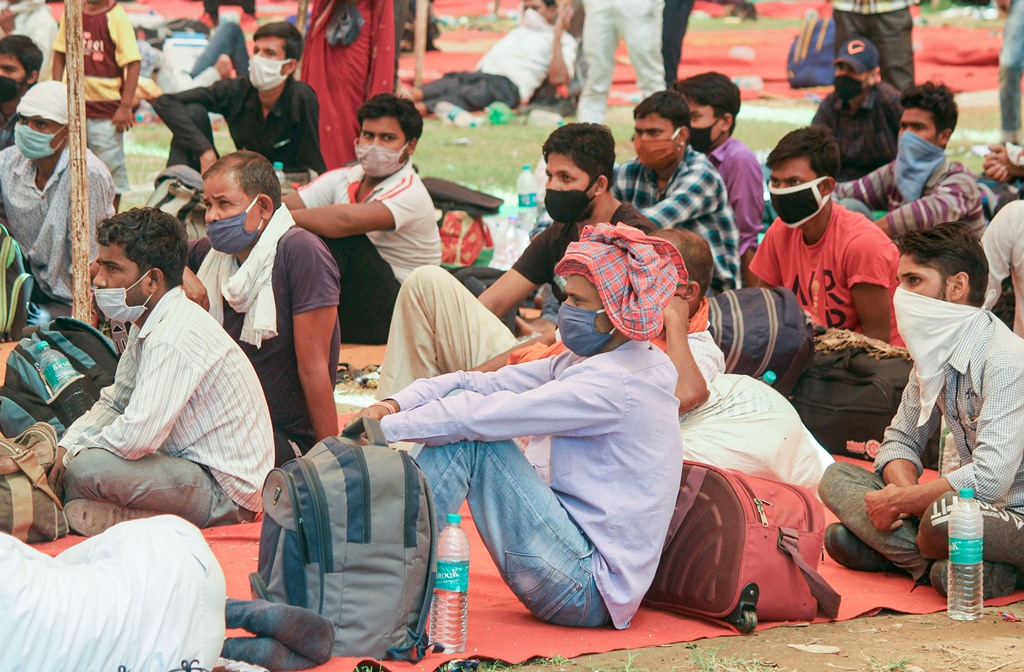 Gurugram: Migrants wait to board a bus for Bihar at Tau Devi Lal Stadium, during the ongoing COVID-19 lockdown, in Gurugram, Tuesday, June 2, 2020. (PTI Photo)(PTI02-06-2020_000216B)