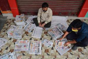 Vendors arrange different vernacular newspaper before delivering it to customers during the nationwide lockdown in Guwahati. PTI Photo