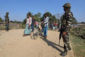 Villagers walk past Central Reserve Police Force (CRPF) personnel patrolling a road ahead of the publication of the first draft of the National Register of Citizens (NRC) in the Juria village of Nagaon district in the northeastern state of Assam, India, December 28, 2017. REUTERS/Anuwar Hazarika