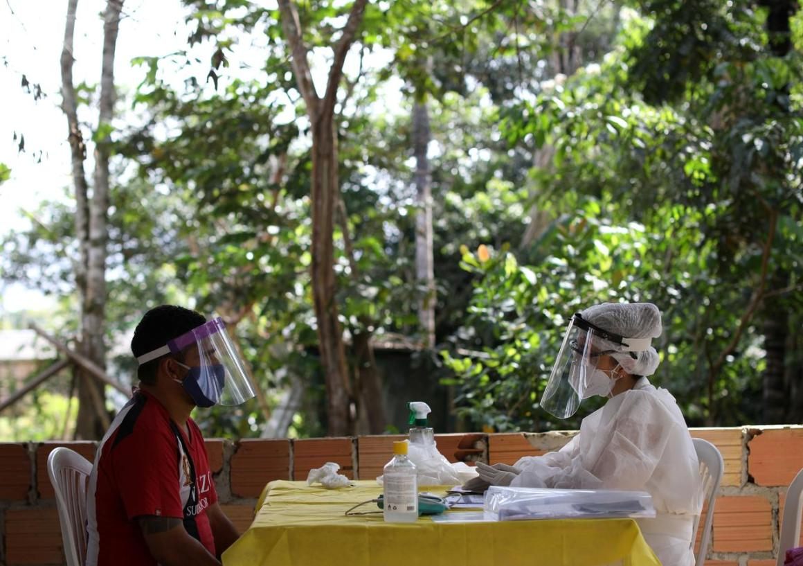A health worker talks with a man before testing for the coronavirus disease (COVID-19), in the Bela Vista do Jaraqui, in the Conservation Unit Puranga Conquista along the Negro River banks, where Ribeirinhos (forest dwellers) live, amid the coronavirus disease (COVID-19) outbreak, in Manaus, Brazil, May 29, 2020. REUTERS/Bruno Kelly