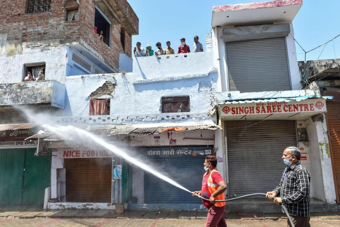 Nagar Nigam workers sanitize an area sealed to contain the spread of COVID-19, in Lucknow, Thursday, April 9, 2020. | Photo Credit: PTI