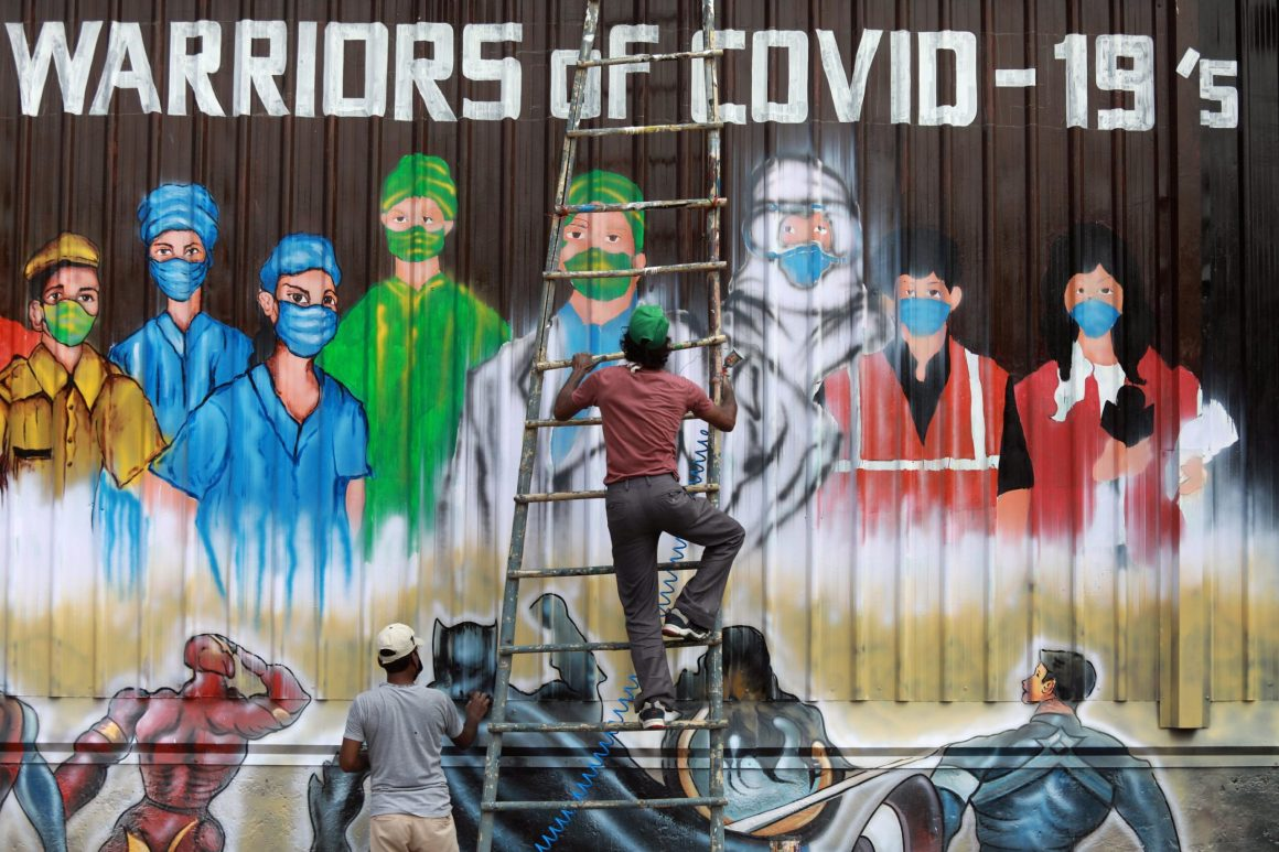 A man gets off a ladder as he completes a mural paying tribute to 'COVID-19 warriors' as India eases lockdown restrictions that were imposed to slow the spread of the coronavirus disease (COVID-19), in New Delhi, India, June 8, 2020. REUTERS/Anushree Fadnavis TPX IMAGES OF THE DAY
