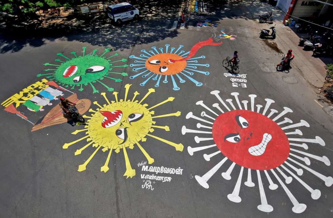 People move past graffiti on a road depicting the coronavirus as an attempt to raise awareness about the importance of staying at home during a 21-day nationwide lockdown to slow the spreading of the coronavirus disease (COVID-19), in Chennai, April 13, 2020. REUTERS/P. Ravikumar