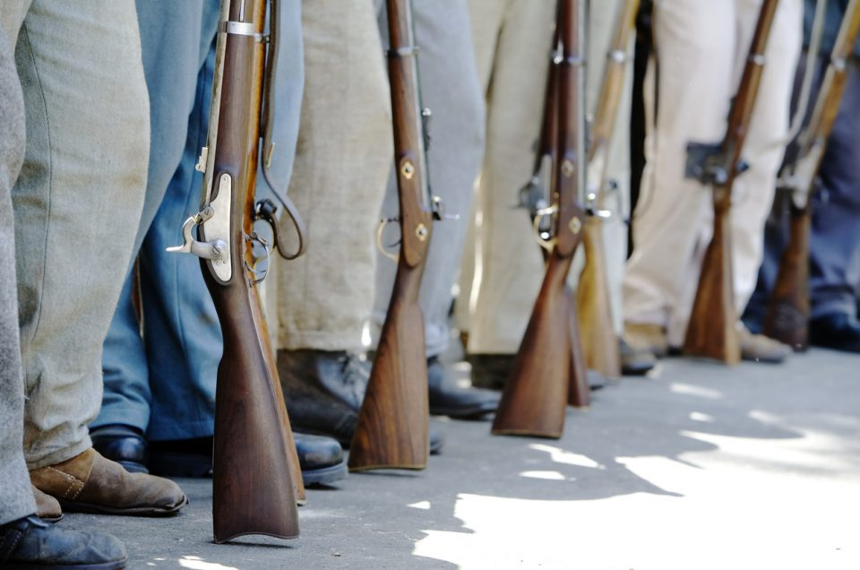 Civil War re-enactors  with period guns stand in a row.
