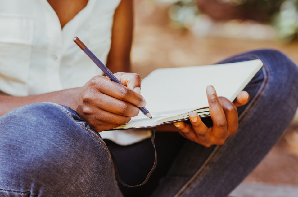 Cropped view of young attractive black woman working, making notes and sitting in park