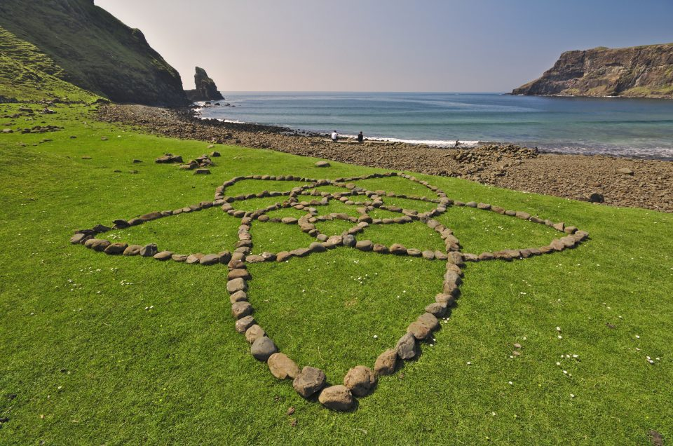 Isle of Skye, Scotland - Stones arranged in the shape of a flower on green grass with Talisker Bay in the background