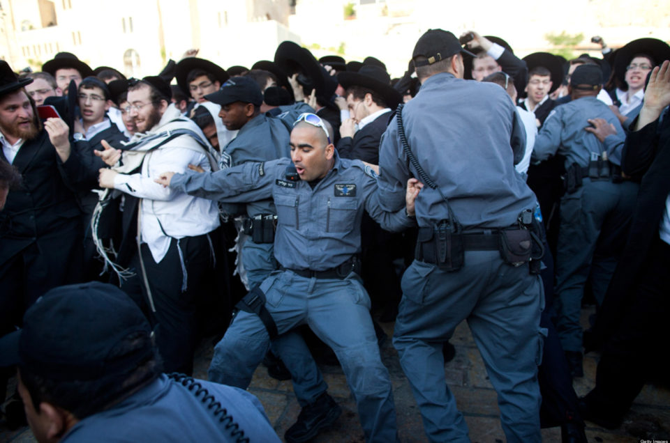 JERUSALEM, ISRAEL - MAY 10:  Israeli police officers attempt to block ultra-Orthodox protestors from members of the religious group 'Women Of The Wall' holding a prayer service to mark the first day of the Jewish month of Sivan at the Western Wall on May 10, 2013 in Jerusalem, Israel. Thousands of ultra-Orthodox protestors clashed with Israeli police during the first monthly prayer service to be held by Women Of The Wall following the recent landmark ruling by Jerusalem District Court allowing women to wear prayer shawls at the Western Wall.  (Photo by Uriel Sinai/Getty Images)