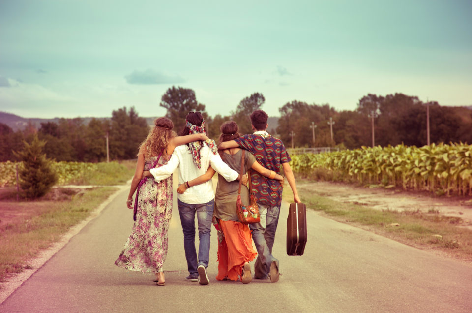Teenage hippie group walking on the road.