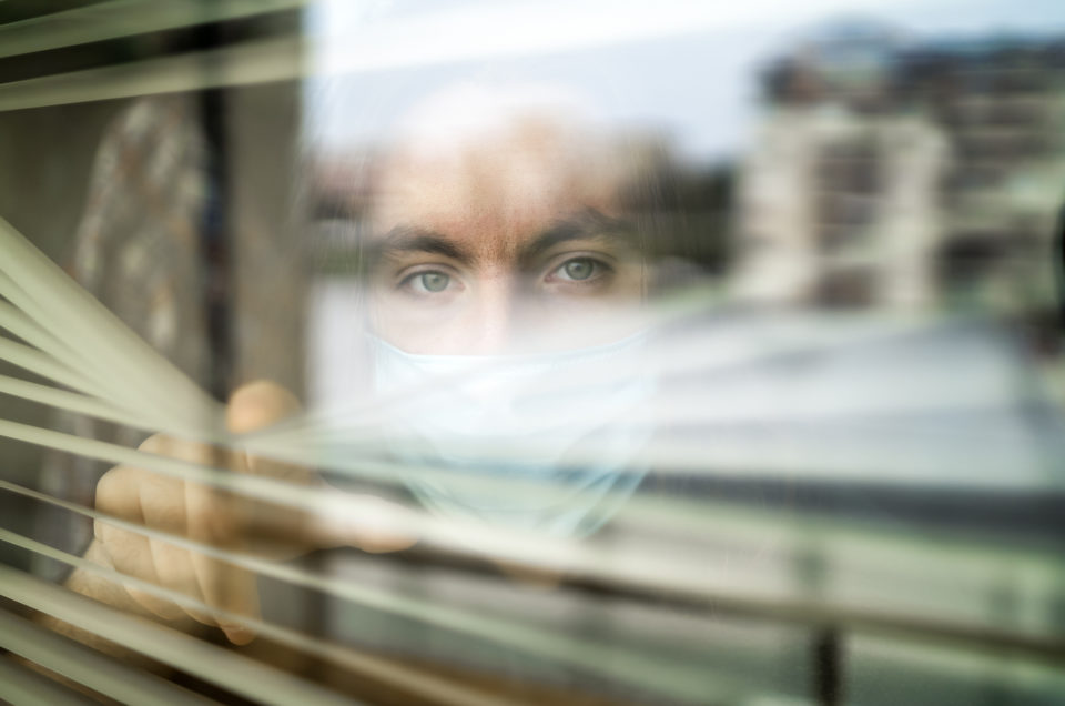 Concerned Healthcare worker looking through a window