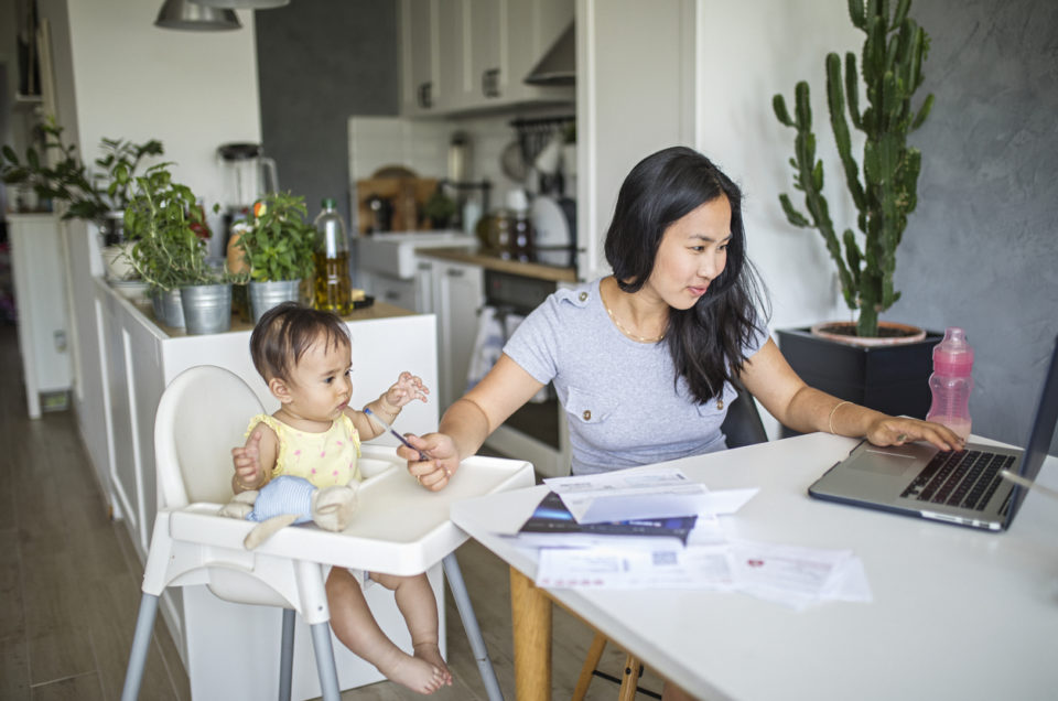 Young Asian mother working and spending time with baby at home