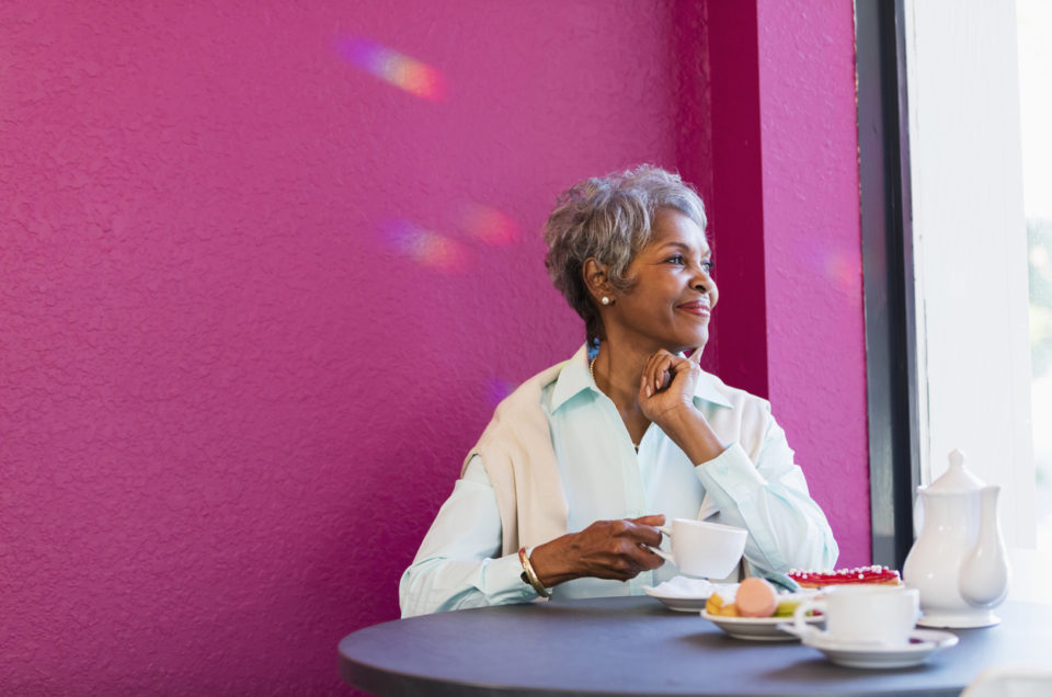 A senior African-American woman in her 70s sitting at a table in a coffee shop, having coffee and pastries, smiling as she looks out the window.