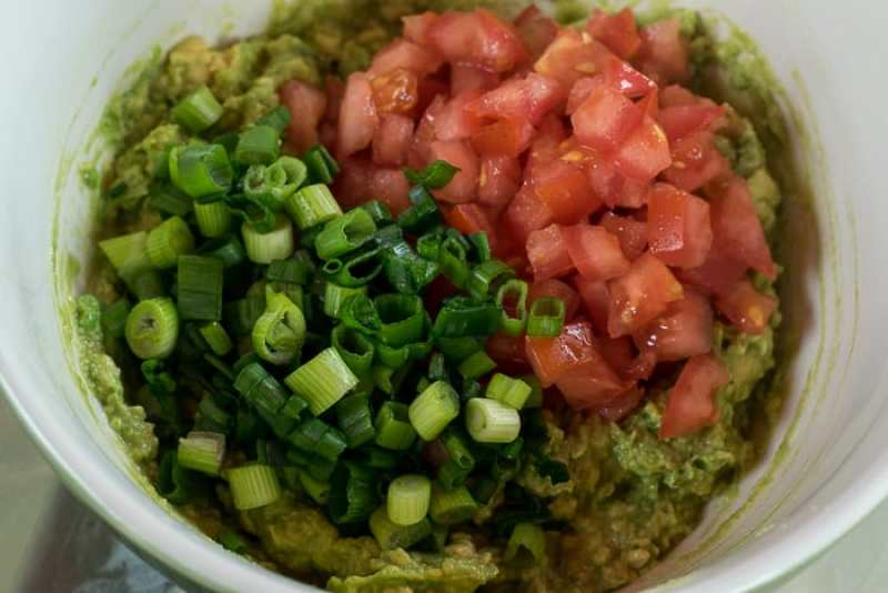picture of mashed avocado topped with diced tomato and sliced green onion