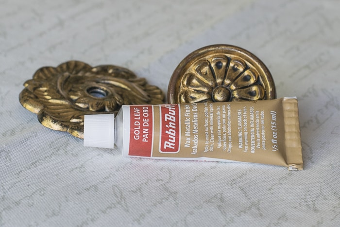 Picture of tube of rub'n buff in front of hardware