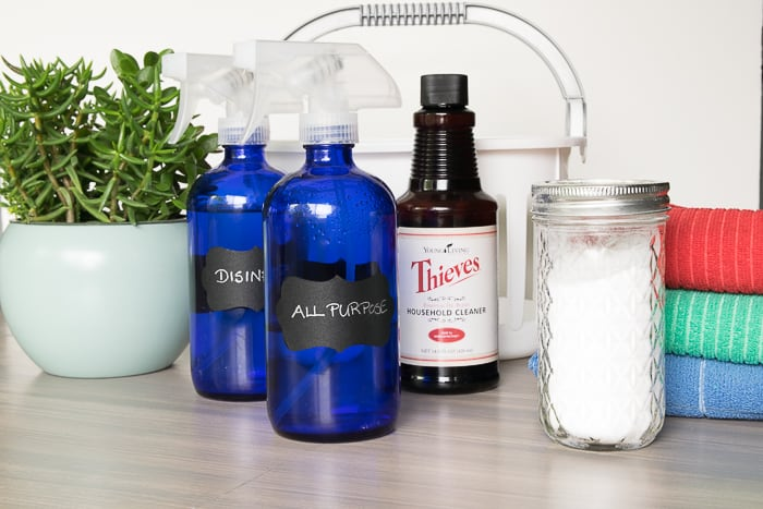 picture of glass spray bottles thieves household cleaner baking soda in jar cleaning cloths and basket