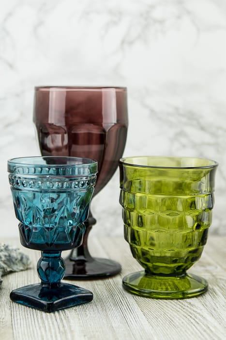 picture showing three pressed glass goblets in blue, green and purple, various heights and patterns