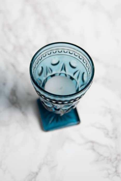 picture showing small blue pressed glass goblet containing a tea light