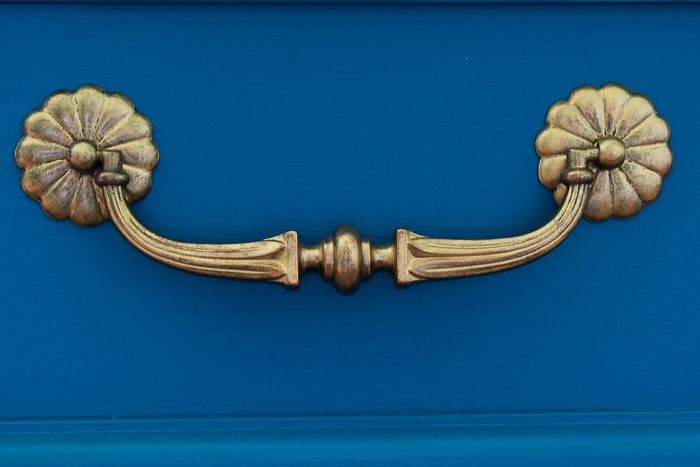 picture of restored brass hardware on teal dresser front