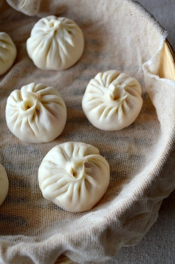 Soup dumplings in steamer before cooking, by thewoksoflife.com