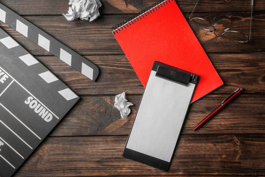 Composition with movie clapper, clipboard and notebook on wooden background, top view