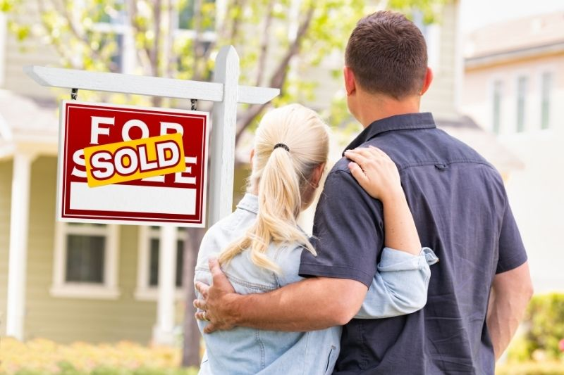 a millennial couple facing the front of sold house