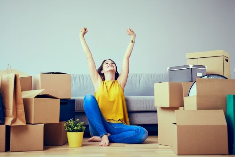 a happy young woman moving to new home
