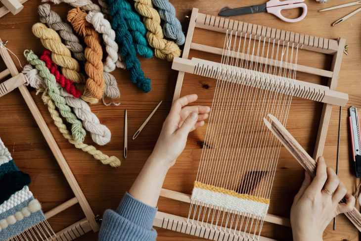 top view photo of person weaving using hand loom