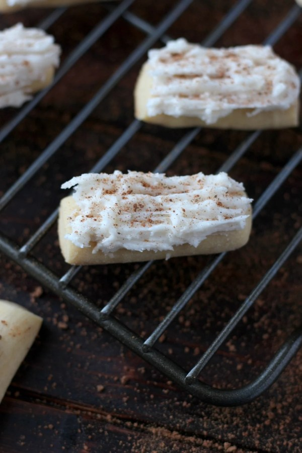 Rum-Buttered Nutmeg Logs - a luxurious Christmas cookie covered in rum-buttered frosting and a dusting of nutmeg! thewoodenskillet.com