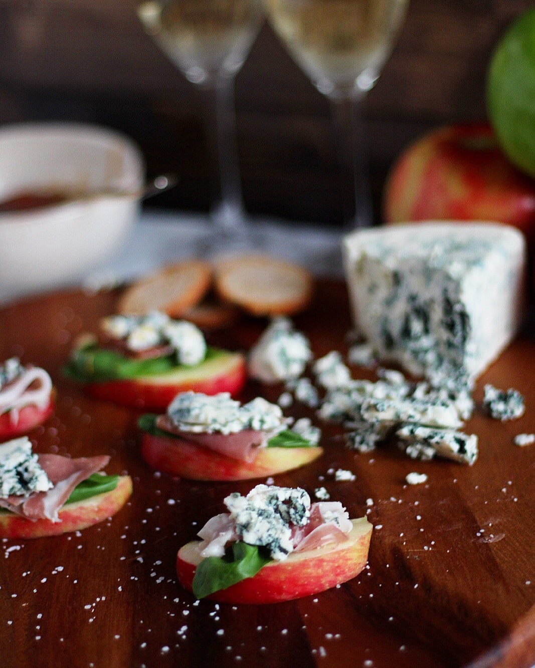 Simple Apple Wedge + Basil, Prosciutto and Blue Cheese with Pear-Infused White Balsamic Glaze. A simple and classy appetizer for your next holiday party! thewoodenskillet.com #foodphotography