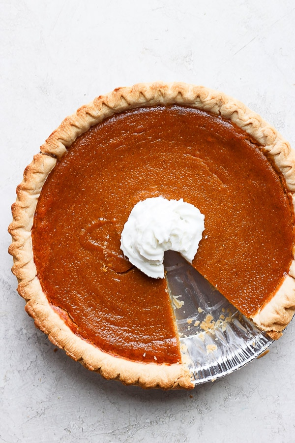 Dairy free pumpkin pie with whipped coconut cream in the center and a piece cut out.