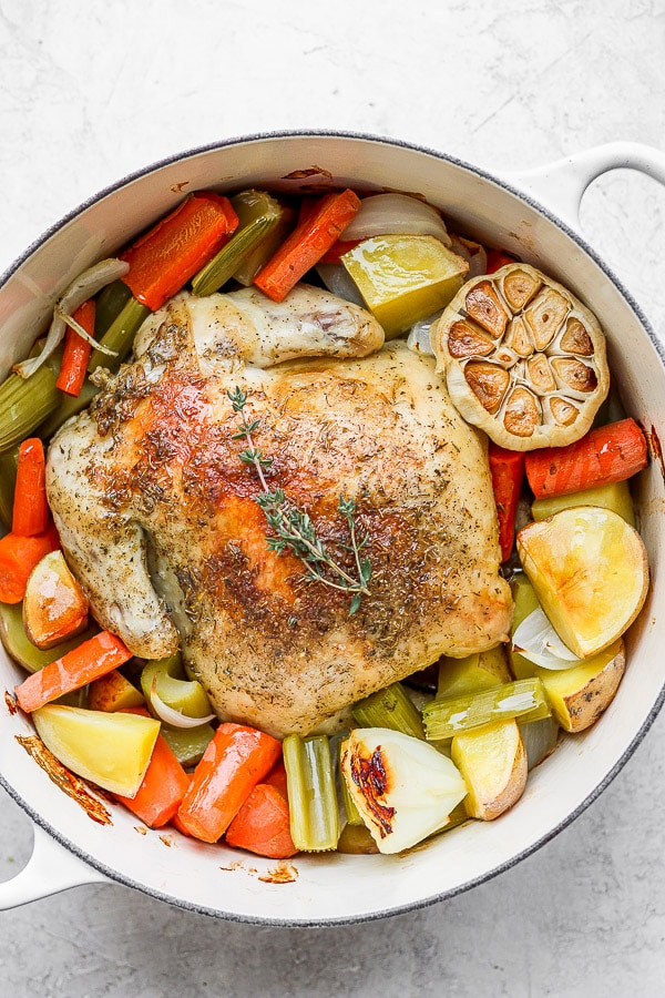 Whole roasted chicken in Dutch oven with veggies and potatoes.