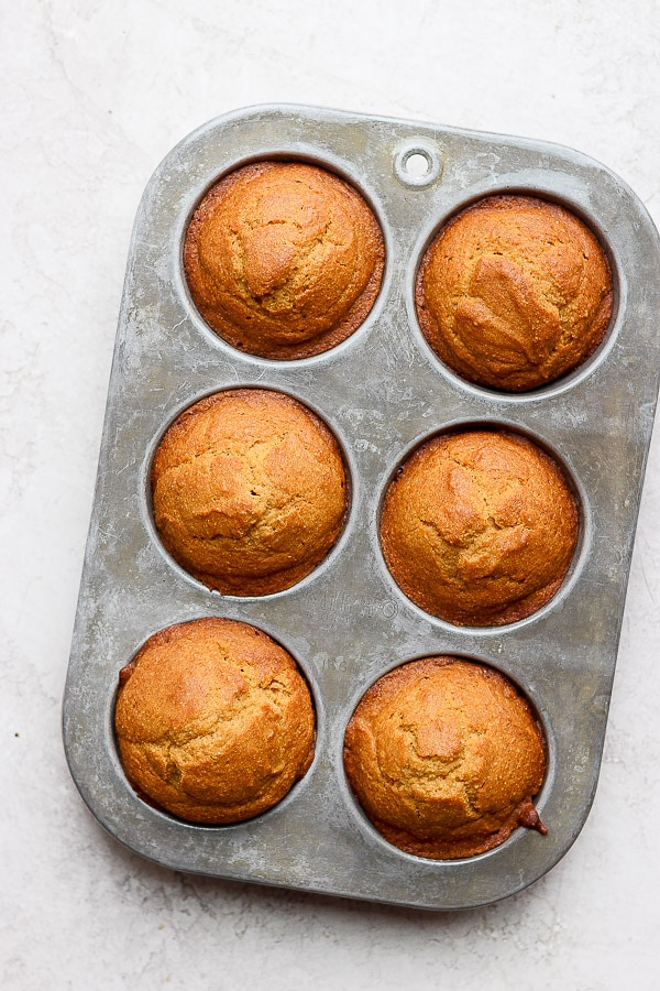 Baked cornbread muffins in a silver muffin tin.