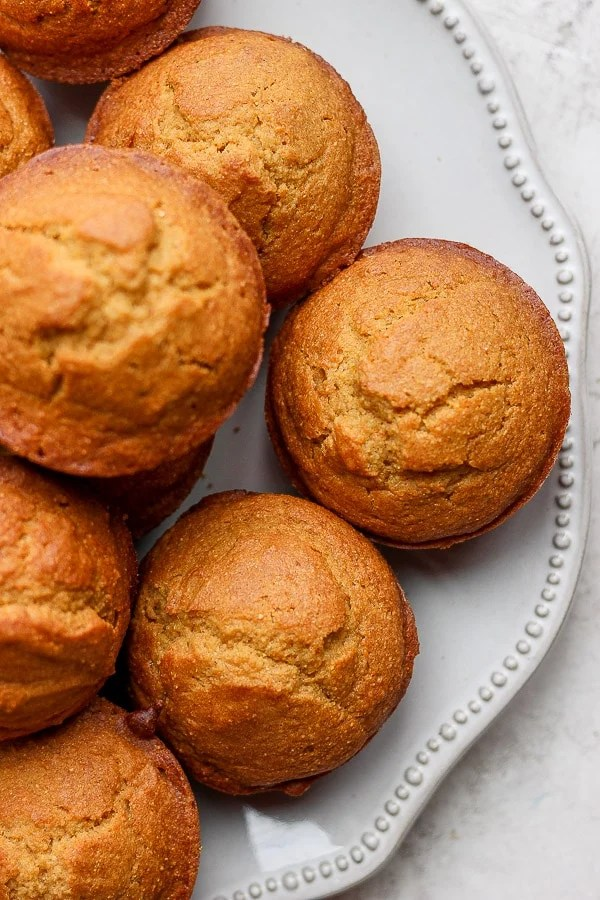 A pile of cornbread muffins on a white plate.