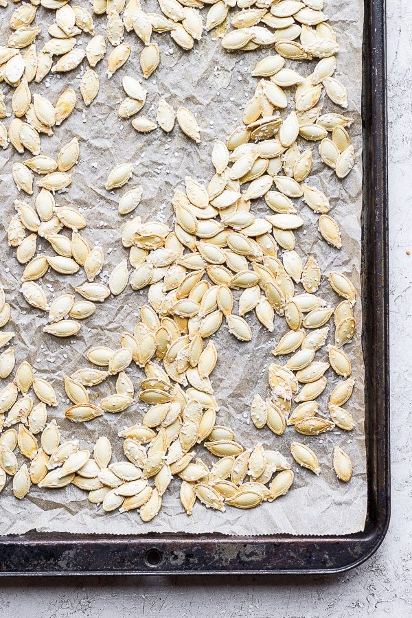Pumpkin seeds on a parchment-lined baking sheet that has been roasted in the oven.