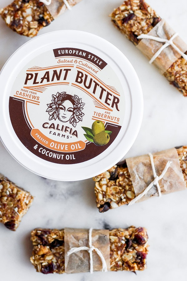 Top shot of a container of Califia Farm Plant Butter surrounded by trail mix bars.