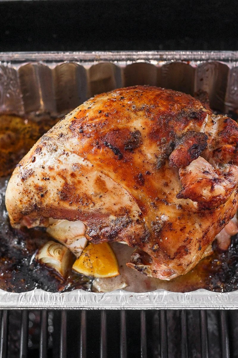 A cooked turkey breast in an aluminum tray on the grill.