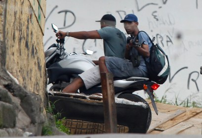 An alleged drug trafficker aims a weapon while escaping in a motorcycle at the Complexo do Alemao in Rio de Janeiro, Brazil, Saturday, Nov. 27, 2010. Occasional gunfire broke the tense stillness Saturday morning as armored vehicles prepared to push past barriers into Rio's most dangerous slum, as police increased pressure on drug traffickers believed to have ordered the wave of violence that has terrorized the city this week. (AP Photo/Felipe Dana)