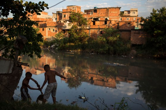 In this Sunday, July 14, 2013 photo, youth play alongside a polluted river in the Varginha area of the Manguinhos slum complex where Pope Francis is expected to visit during his trip next week to Rio de Janeiro, Brazil. In one of the key events of his trip, the church's first Jesuit leader will venture into this rough slum that sits along a violence-soaked road known by locals as the Gaza Strip. (AP Photo/Felipe Dana)