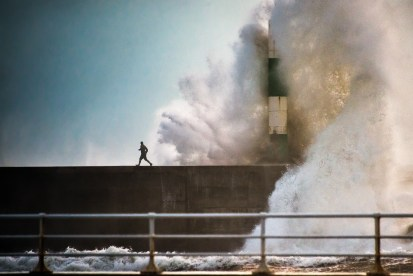 A man escapes a huge wave at Aberystwyth Lighthouse in Wales, by Craig Kirkwood