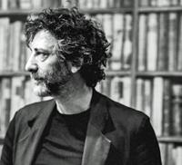 Neil Gaiman in front of a bookshelf.