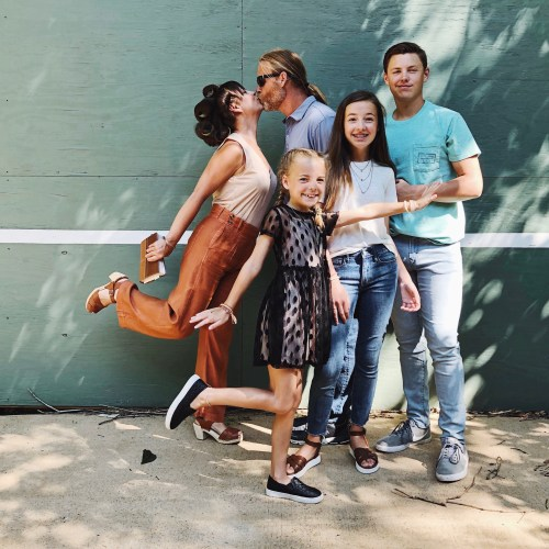 family picture in front of tennis wall with kids and mom and dad kissing