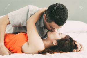 Closeup of passionate couple embracing and kissing in bed.