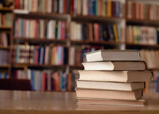 Close up of books on desk in library.