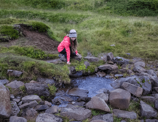 Travel blogger girl drinks from a natural spring. A secret drinking spring along Snaefellesness Peninsula is not on the Ring Road, but worth the stop on your Iceland itinerary.