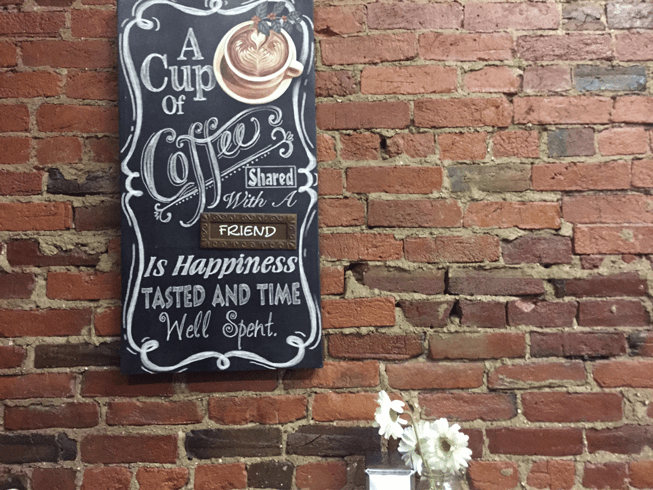 A cup of coffee quote and sign