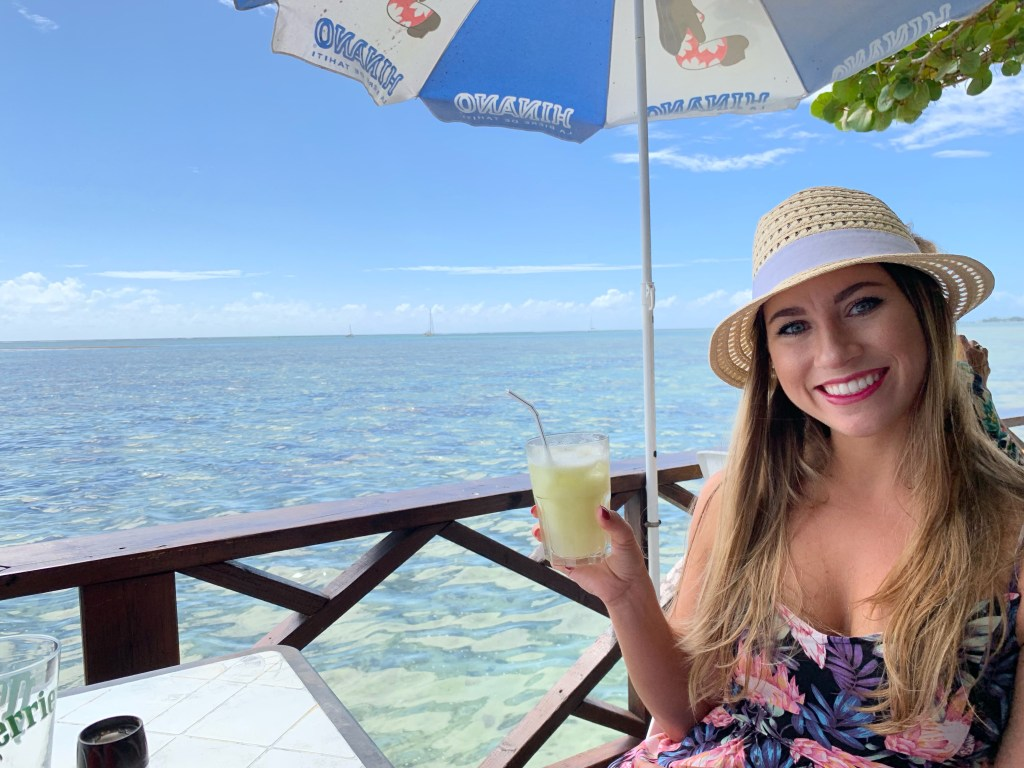 Travel blogger Amanda enjoys fresh squeezed grapefruit juice at Snack Mahana in Moorea looking over the ocean. Snack Mahana is one of the best restaurants in Moorea.